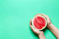Half of Sweet Mini Watermelon in Female Hands with Green Copy Space.  Royalty Free Stock Photo