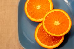 A half tangerine or an orange on a table. Close-up. Soft focus. Top view. Copy space. Citrus. A mandarin is served on a blue plate. A half tangerine or an orange stock photography