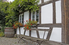 Half-Timbered House With Bench. A wooden bench in front of antique half-timbered European private house, partially overgrown by a climbing plant Royalty Free Stock Images