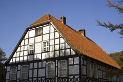 Half-timbered house in black and white with red tiles. In front of a forest in autum colors Stock Photo