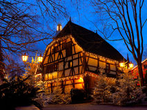 Half-timbered house Christmas magic by night. A Fachwerkhaus decorated with fairy-lights and Christmas trees placed in the street, lighted by night. Christmas Stock Photo