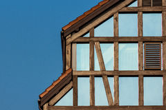 Half-timbered house with glass wall. Fragment of a half-timbered house made of glass with a background of blue sky.  The sky is reflected on a glass wall of the Royalty Free Stock Image