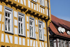 Half timbered house with rooftop dishes Stock Images