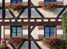 Half-timbered house with several window shutters and flowers Royalty Free Stock Photos