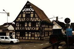 Street traffic in front oft he Half-timbered house. A half-timbered house with a striking beam construction at the corner of a crossroads with street traffic Stock Images