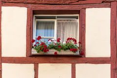 Half-timbered house with window shutters and flowers Stock Photos