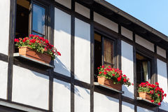 Half-timbered house with window shutters and flowers Stock Photo