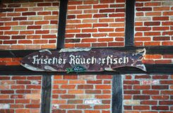 Half-timbered wall with an old wooden plaque hanging on it indicating the sale of fresh smoked fish