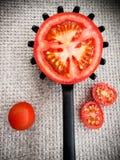 Half tomato on a black plastic kitchen spoon. stock photography