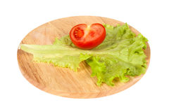 Half of tomato and lettuce on a cutting board. On an isolated background Stock Photo