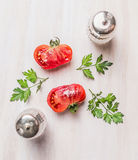 Half of tomatoes with herbs and salt and peppers on white wooden background, top view, simple food Stock Photography