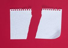 Half torn blank white sheet in a cell on a red background stock photo