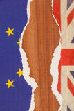 Half torn union jack and european union paper flag. On wooden background stock images