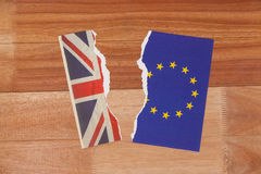 Half torn union jack and european union paper flag. On wooden background stock image