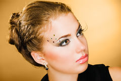 Half-turn portrait. Pretty model with art make up on brown background Stock Image