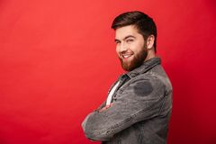 Half turn portrait of attractive man in jeans jacket posing on c. Amera with amazing smile and arms folded isolated over red background Royalty Free Stock Image