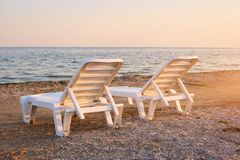 Half-turn view chaise longues on the beach. Beach chaise longues on the morning Stock Photo