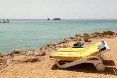 Half turn view chaise longues on the beach beach chaise longues. On the summer stock image