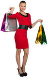 Half turned smiling woman handing bags up Stock Photography