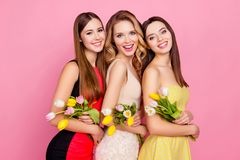 Half turned three pretty, trendy, laughing girls with beaming sm royalty free stock images