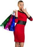 Half-turned woman covering mouth, handing bags Royalty Free Stock Photos