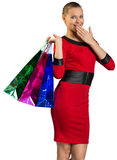 Half-turned woman covering smile, handing bags Stock Photography