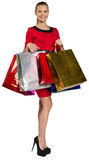 Half turned woman holding bags in two hands Stock Photo