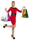 Half turned woman with right leg up handing bags Stock Photos
