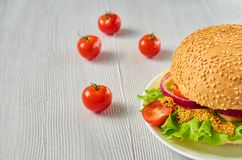 A half of veggie burger with salad, onion rings decorated with fresh cherry tomatoes on the gray concrete background. With free copy space. Vegetarian sandwich Royalty Free Stock Photos