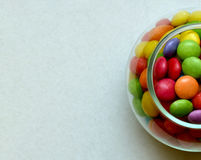 Half-view of jar with colorful candies on grey background. Top view. Festive background for modern design. Close-up of multicolored candy in a glass, isolated Royalty Free Stock Images