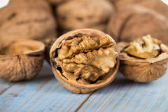 Half walnut kernel and whole walnuts on a wooden background Royalty Free Stock Photos