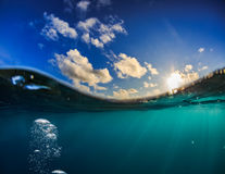 Half water shot of ocean water and sky with the sun above Royalty Free Stock Image