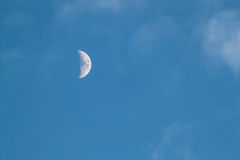 Half waxing Moon in blue sky. Before sunset Stock Photo