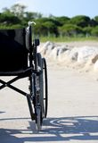 Half wheelchair near the beach with vegetation in the background Royalty Free Stock Image