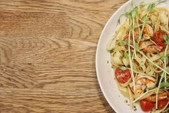 Half of a white dish with shrimp scampi and linguine in on a wood table from top view. Half of a white dish with shrimp scampi and linguine in on the right of a Stock Image