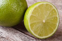 Half and whole fresh juicy lime on background wooden Royalty Free Stock Image