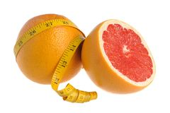 A half and a whole grapefruit wrapped with measure tape on white. Background isolated Royalty Free Stock Photography