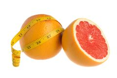A half and a whole grapefruit wrapped with measure tape on white. Background isolated Stock Photo
