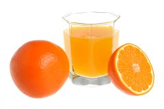 A half and a whole orange with a glass filled with citrus juice Royalty Free Stock Images