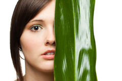 Half of woman's face with green leaf Stock Photos