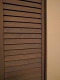 Half of a Wood Closet door. Hald of a brown wood closet door with yellow painted wall stock photography