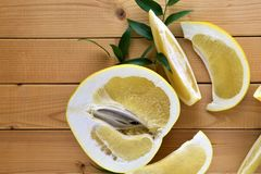 A half of pomelo and it`s cut pieces on wooden background with green leafs, cut pomelo close up. A half of yellow fresh pomelo and it`s pieces on simple wooden Stock Photography