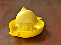 Half of yellow lemon in the juicer on brown table background. stock photos