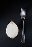Half a yellow onion with stainless steel fork Royalty Free Stock Photography