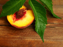 Half yellow peach on wooden background Stock Image
