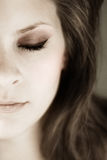 Half young womans face with eyes closed. Portrait of half a young womans face with eyes closed in muted tones stock photos