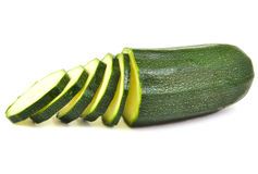 Half zucchini with some slices on white background. Royalty Free Stock Photography