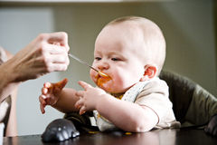 Halfjaarlijkse oude baby die stevig voedsel eet Royalty-vrije Stock Afbeelding