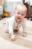 Halfjaarlijkse oude baby op het tapijt Stock Foto