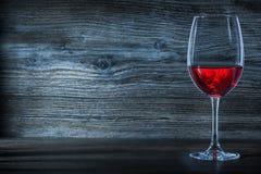 Halflinevinglas med rött vin på tappningträ arkivbild